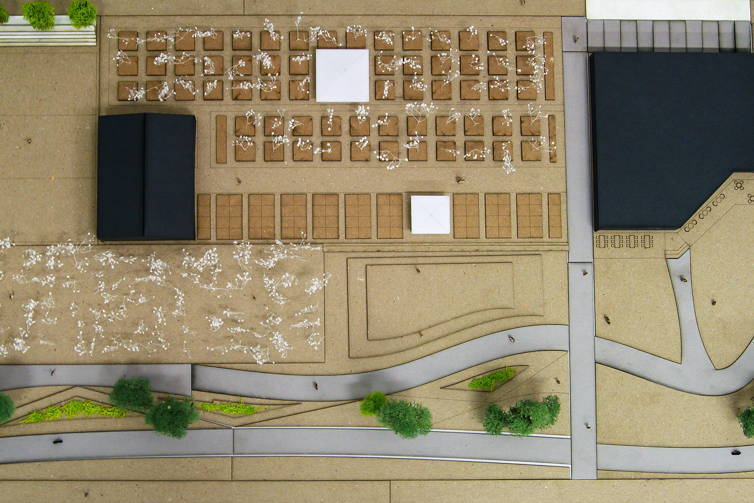 A model shows planters for gardens and trees, terraced seating, and walking and bike paths.